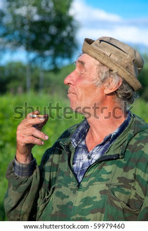 A man in camouflage smokes a cigarette