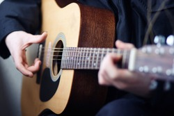 A man in dark clothes playing acoustic wooden six-string guitar beautiful melodies and songs