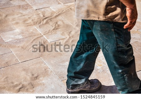 A man in dirty clothes walks across travertine tiles covered in sand #1524845159