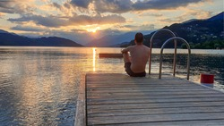 A man in full cup sitting at the end of a wooden pier of Millstaetter lake and enjoys the sunset. The sun sets behind high Alps. Calm surface of the lake reflects the orange sky and the mountains