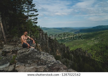 A man in glasses with a bare torso and barefoot looking into the distance, sits on the rock #1287022162
