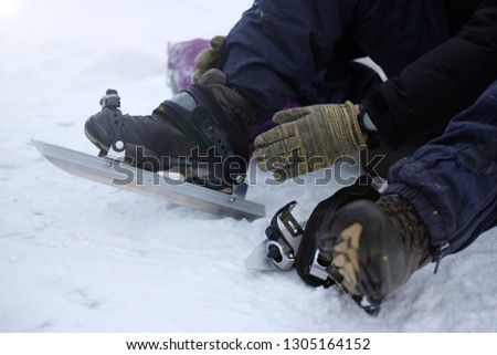 A man in gloves puts on long metal skates for skating on the ice in winter, the theme of sports and recreation  #1305164152