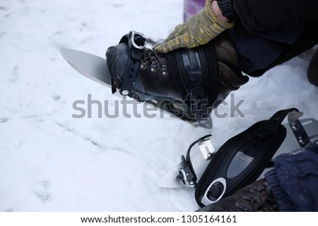 A man in gloves puts on long metal skates for skating on the ice in winter, the theme of sports and recreation  #1305164161