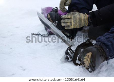 A man in gloves puts on long metal skates for skating on the ice in winter, the theme of sports and recreation  #1305164164
