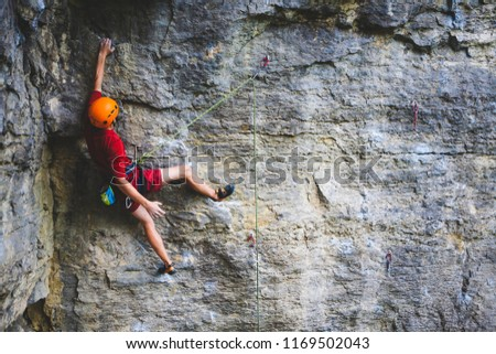 A man in helmet climbs the rock. Climbing in nature. Fitness outdoors. Active lifestyle. Extreme sports. The athlete trains on a natural relief. Training in a picturesque place. Climbing in Turkey.