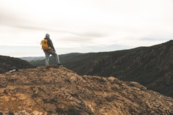 A man in hiking clothes with a yellow backpack stands on the top of a hill among the mountains around and in the background