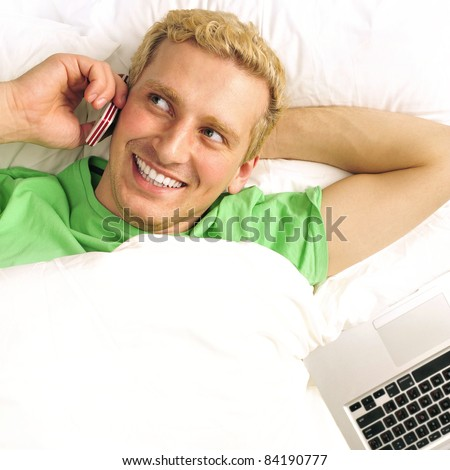 A man in his bed speaking cell phone and looking away