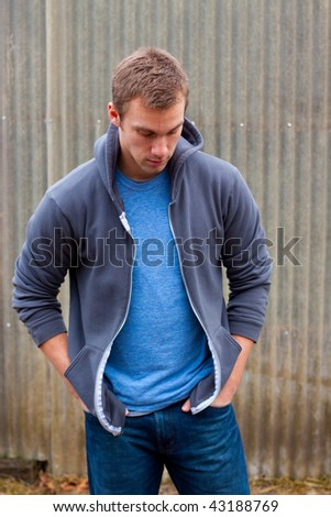 A man in his mid-20's poses for some lifestyle portraits in fashionable outfits outdoors.