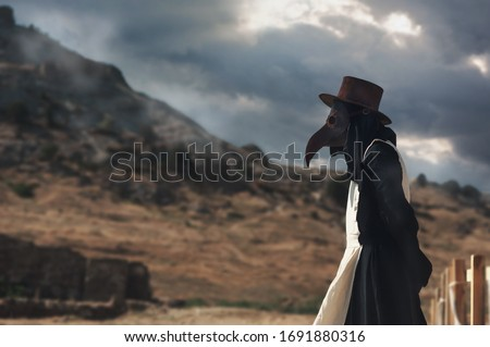 A man in historical masquerade costume of plague doctor in old grange castle near the mountains. Epidemia protection costume. Pandemia horror mystical fantasy plague doctor Stockfoto ©