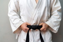 A man in kimono is holdong his black belt and staying near a wall of a gym