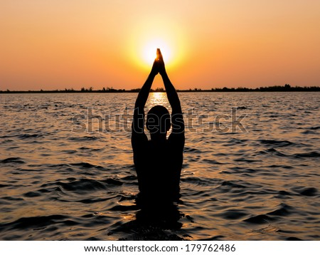 A man in meditation and prayer as he stand in a holy river at dusk