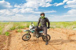 A man in motorcycle equipment sits on an enduro motorcycle. Motocross sport. Extreme off-road race.