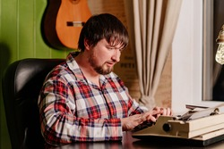 a man in plaid pajamas types on a typewriter at night in his home office. work as a writer. inspiration or muse for the poet. Journalist. Retro.