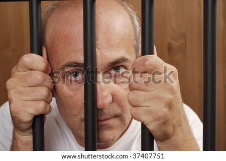 A man in prison holding bars with his hands looking distressed