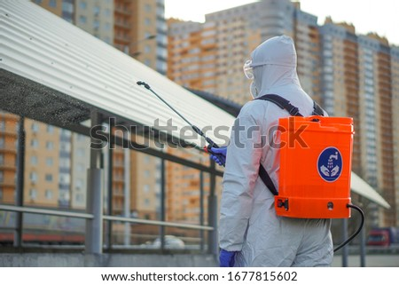 A man in protective equipment disinfects with a sprayer in the city. Surface treatment due to coronavirus covid-19 disease. A man in a white suit disinfects the street with a spray gun. Virus pandemic