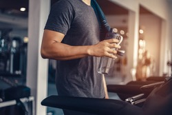 A man in running on treadmill at gym and holding bottle of water