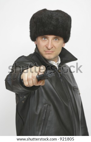A man in Russian clothing complete with a 9mm automatic handgun pointed at the camera