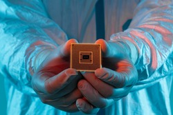 A man in sterile form holds a microprocessor, close-up. Microchip production technology, modern production, special microcircuit. Selective focus