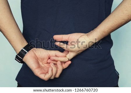 a man in struggling to remove wedding ring from his finger holding hands behind his back. concept of treason. Husband cheats on wife. cheating wife #1266760720