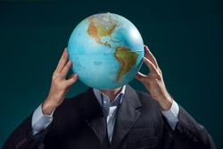 A man in suit holding globe in front of his face. Business, education and idea concept