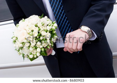 a man in suit with watch hands a flower bouquet