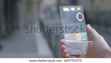 A man in the city, use the transparent phone with the latest technology with holography and watch the weather and the messages. Concept: technology, future and futuristic technology.