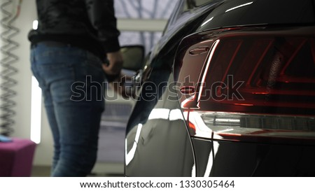 A man in the garage (car service) Checks the car alarm and then goes off (comes in) turning off (turning on) the lights behind him. Concept of: Auto garage, Security.	  #1330305464