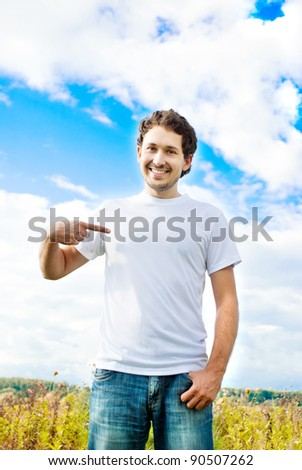 a man in the meadow pointing the finger at himself