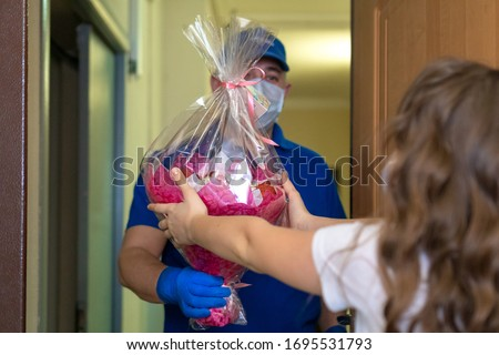 A man in uniform, a medical mask and rubber gloves with a box bouquet in hands, a parcel in his hands. Delivery of gifts and gifts during the quarantine of the coronavirus pandemic. Home delivery