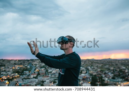 A man in virtual reality glasses on the background of a sunset over the city. Concept of future technologies. Modern technologies. #708944431