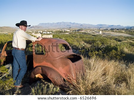 A man in western attire leaning on an old, long abandoned vehicle surrounded by rugged terrain.