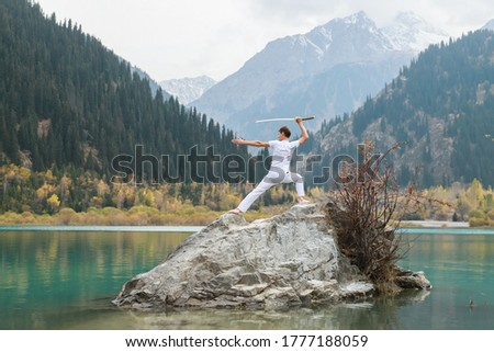 A man in white clothes with a sword stands on a large stone among the highlands. Foto stock ©