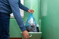 A man in white shirt and blue jean throwing black garbage bag in to plastic green trash.