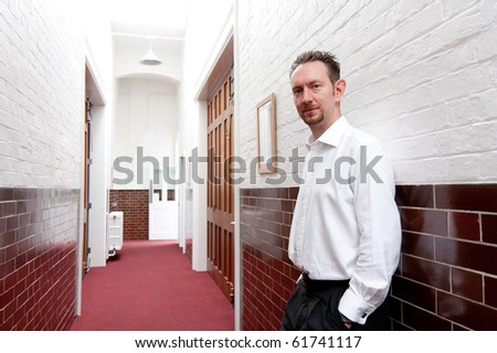 A man in white shirt leans against the wall in a brick and tiled corridor.