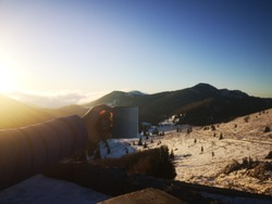 A man in winter jacket is holding cup during beautiful sunrise in the mountains. Northern Velebit National park in Croatia.
