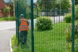 A man in work clothes behind a metal mesh fence. View from the back. Green grass and bushes in summer. Concept - the gardener takes care of the land.