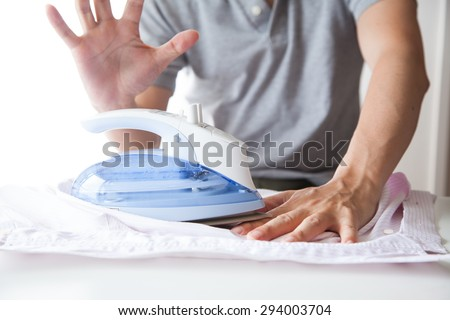 A man ironing his shirts and burning his fingers