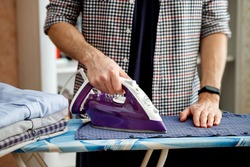 A man irons a shirt on an ironing board with an iron. Daily household chores.