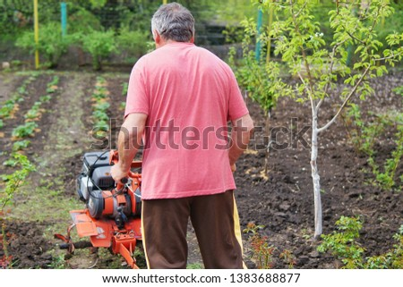 A man is a farmer with a motor cultivator plows a small garden #1383688877