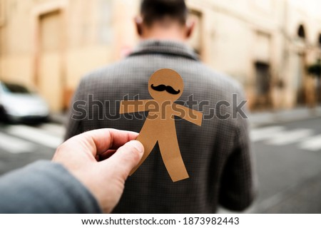 a man is about to attach a paper man doll to the back of another man, as a prank for dia de los inocentes, the innocents day, a feast held in spain and hispanic america equivalent to april fools day Foto stock ©