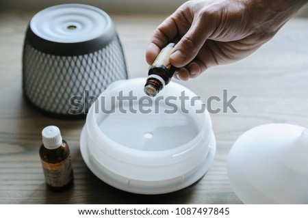 A man is adding essential oil to an aroma diffuser.