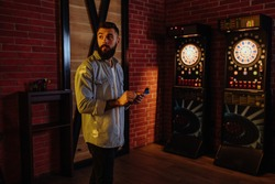 A man is aiming before taking a shot while playing darts
