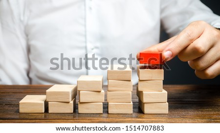 A man is building a ladder or growth chart from blocks. Strategy planning business expansion. Climbing the career ladder. Increase in income, organization of processors. Prioritization. Leadership Zdjęcia stock ©