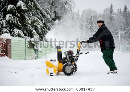 A man is cleaning the country road with snow blower in winter
