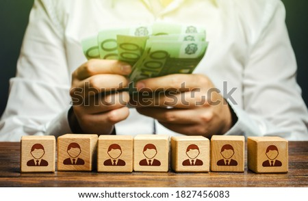 A man is counting euro money in his hands over blocks with symbols of employees. Wage fund. Accounting and budgeting. Payday. Expanding a profitable business, recruiting and training employees. Foto stock ©