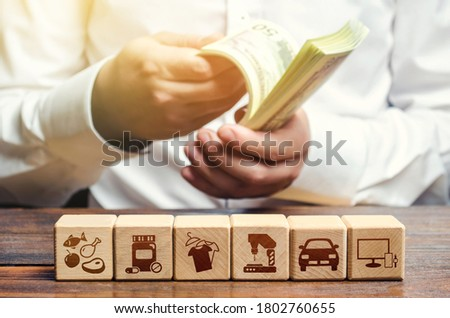 A man is counting money on the background of blocks with goods attributes. Import and export of goods and products. Retail and sales. Trade surplus, high purchasing power. Economic recovery. Foto stock ©
