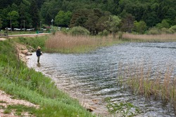 A man is fishing alone by the lake, among the reeds, with a fishing rod. Bolu Abant national park.
