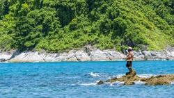 A man is fishing on a rock at the rocky shore.