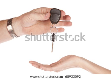 A man is handing a car key to a woman.