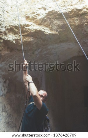 A man is holding a climbing cable in a cave. #1376428709